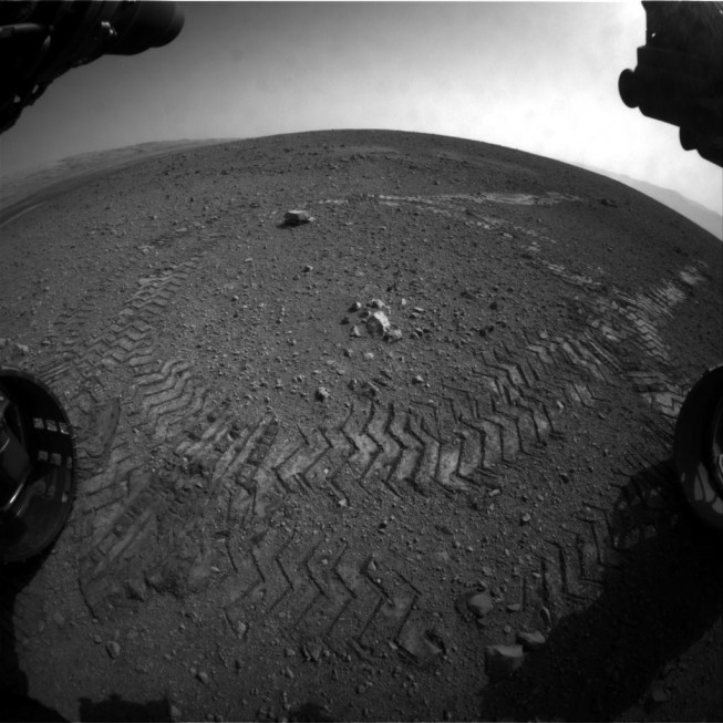Tracks left on the surface of Mars. This picture was taken using one of the hazard avoidance cameras, which is equipped with a fisheye lens. Photo: NASA/JPL-Caltech.