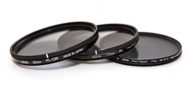 "Three polarizing filters. Two are circular, one is linear. On the right is the ""slim"" version. Note how it is visibly slimmer than the other two. All the filters have a mark on their rotatable part that marks the polarization plane. (Two have a line; the one on the right has a small triangle.)"