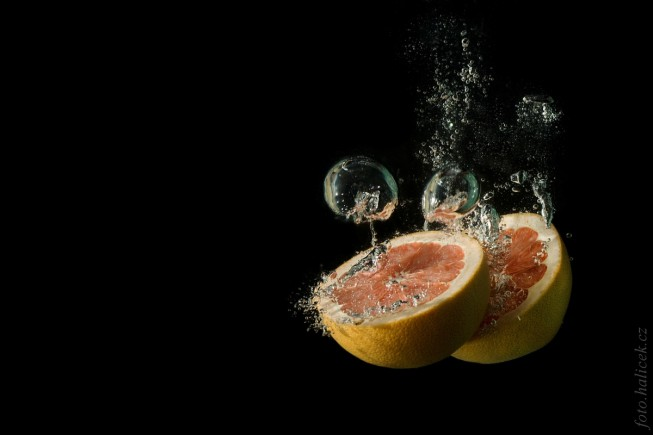 Halved grapefruit. Canon 1000D, EF 75-300 mm při 80 mm, 1/200 s, f/9.0, ISO 100. Background darkened and cleaned up via digital edits.