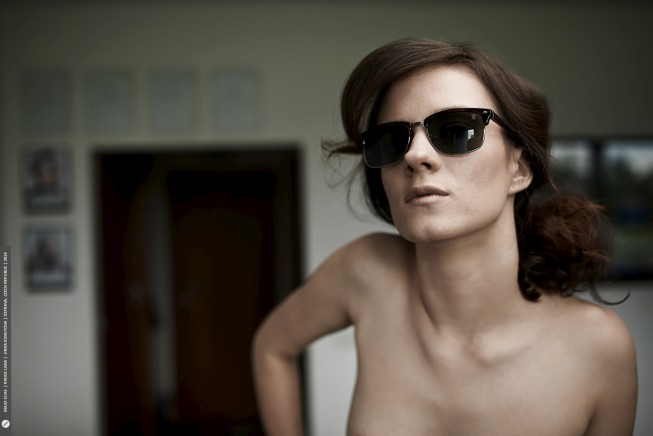 "The glasses and the background are too visible here; this can't really be called a ""naked portrait."""
