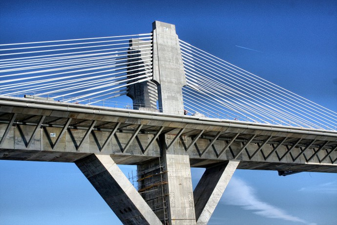 A simple but forceful photo. It captures one portion of a bridge—a pillar. This symmetrical photo is subtly supplemented by the airplane overhead and the figure on the bridge. The coarse grain used also suits it well.