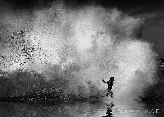 An ocean playing with a boy, in silhouette. The wave is a great finishing touch for the atmosphere—without it, there would be something missing. The photographer found just the right moment. Author: ErolAYYILDIZ