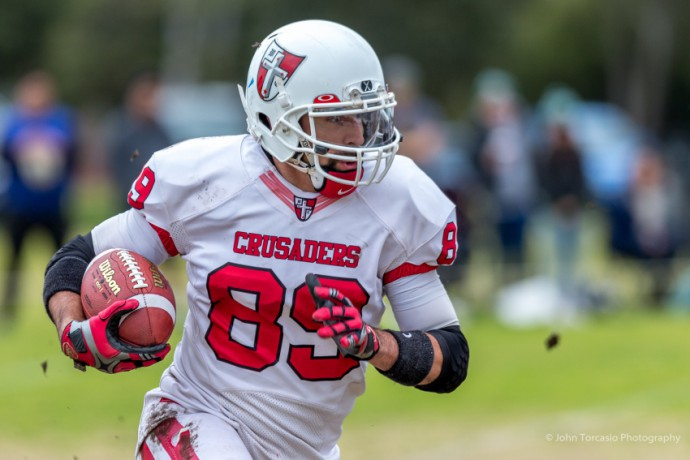 A solid sports photo with superb technical quality and a great depiction of the athlete's expression. The fans in the background and the great use of depth of field add a lot of atmosphere. Photo: Gridiron Victoria : John Torcasio Photography