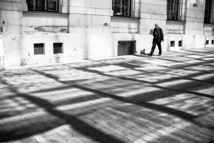 Get rid of the colors and voila, it's like the person has been peeled out of the picture. This is helped by the contrast of the dark clothing and the brighter background. The line formed by the bases of the houses running parallel to the shadows on the sidewalk adds dynamics and a feeling of motion; its role becomes more important in black-and-white.
