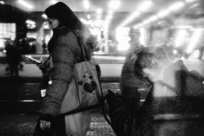 A black and white preview suppresses all the distracting swaths of color. That lets other things shine through: the line of lights from the shopping center, opposite to the line formed by the tilts of both women's heads. This composition guides the viewer's eyes from one woman to the other and doesn't force them to wonder if the woman on the right is also searching for her phone like the one on the left.