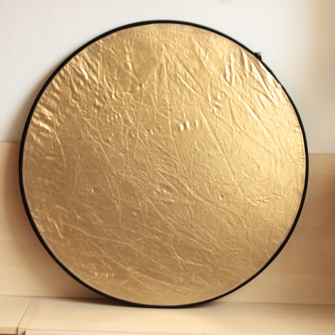Use a gold reflector to make natural light warmer. But don't overdo it; the effect is fairly strong. Ideally you want to simulate the evening light during daytime.