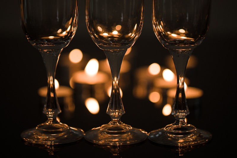 Three glasses side-by-side. Their shapes are only visible because the candlelight from the background is refracted in them. Canon 5D Mark IV, Canon EF 100/2.8 IS MACRO, 1/50 s, f/2.8, ISO 200, focal length 100 mm