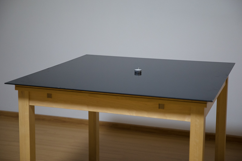 A table for experiments. A black-glass tabletop creates a slightly mirrored image.