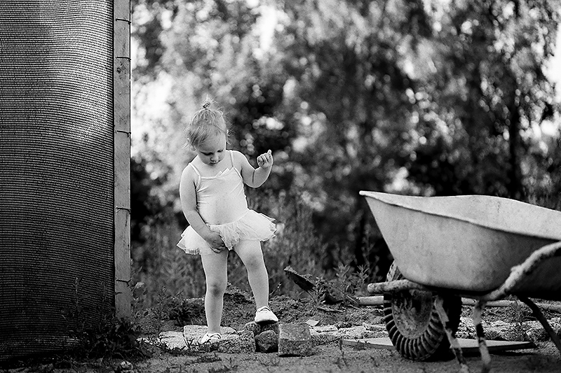 "I happened to be in the garden when my daughter ran out to show off the ""outfit"" that she and her sister had created. I had my camera with me, and so I took a few shots, but they weren't turning out. But after that I got to talking with my neighbor, and my daughter started exploring the garden. I then caught her in this ""ballet"" pose. Canon EOS 6D, Canon EF 100/2.8, 1/400 s, f/3.2, ISO 200, focal length 100 mm"