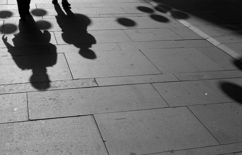 I noticed some interesting rounded sidewalk shadows from lamps hung across the street. But there were a lot of people walking this way, and they often covered up the shadows. It took a bit of waiting until an opening appeared with fewer people. Olympus OM-1, F.Zuiko Auto-S 50 mm f/1.8, Ilford PAN 400