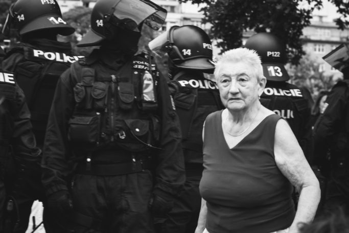 7 Challenges of Reportage Photography: granny ahead of a row of policemen.