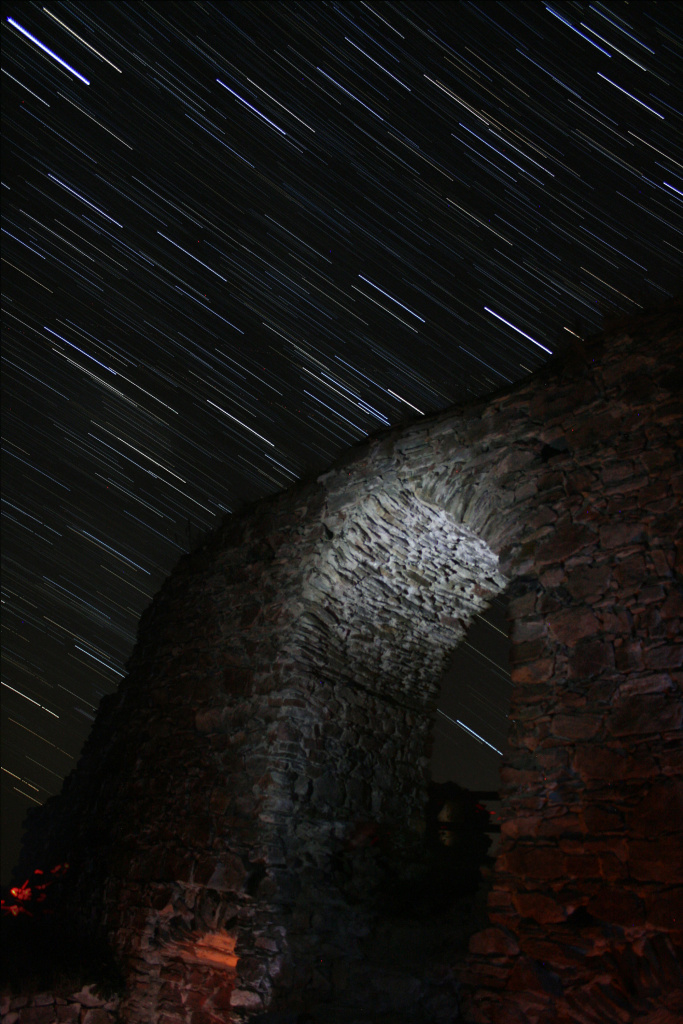 How to photograph star trails: starry sky over a gate.