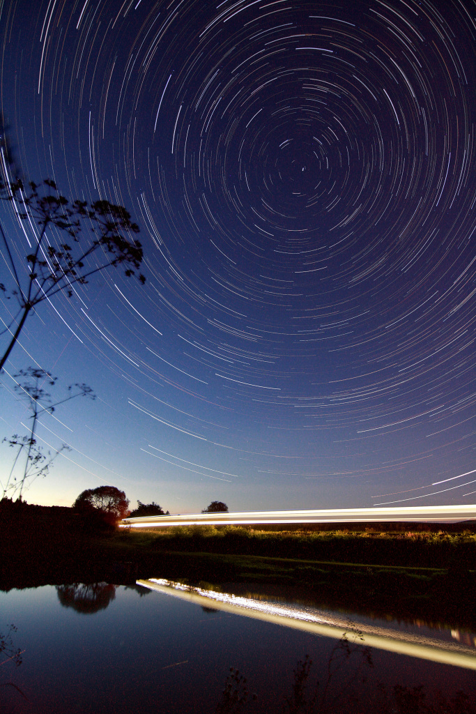 How to photograph star trails: stars and a passing train.