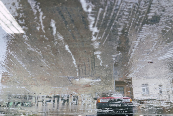 Discover the Wonders of Winter City Photography: reflection in a puddle.