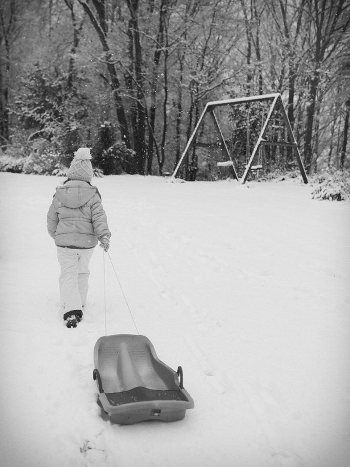 How to Photograph Children in Winter in Winter: A softly toned photo accentuates the falling snow.