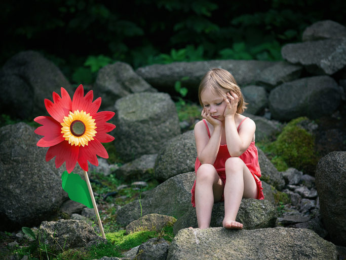 Photographing Kids in Colors and Black and White: a synthetic flower and a child sitting on stones.