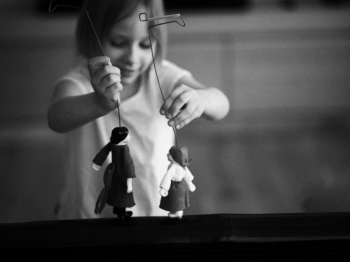 Photographing Kids in Colors and Black and White: child playing with puppets.