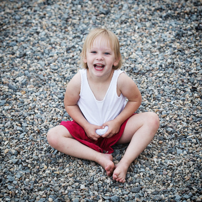 Photographing Kids in Color and Black and White: Neutral colors of stones in combination with red.