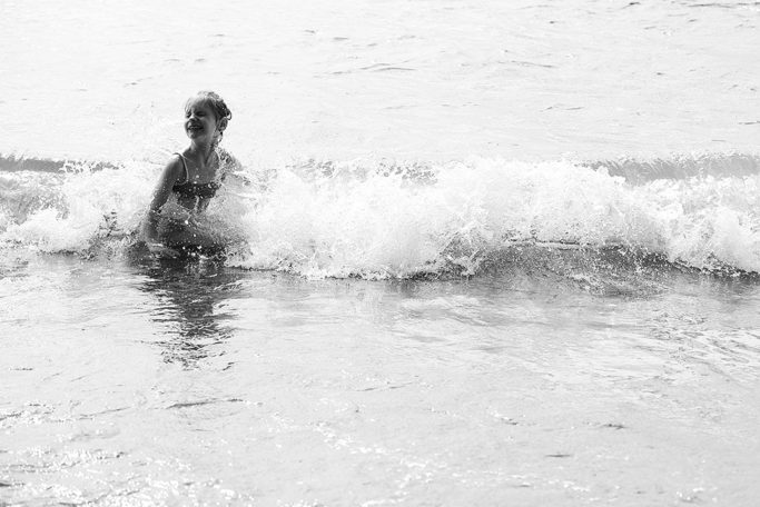 Photographing kids against the light: child enjoying the sea.