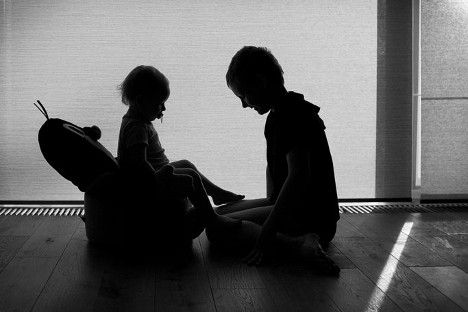 Photographing kids against the light: the partial silhouette of siblings.