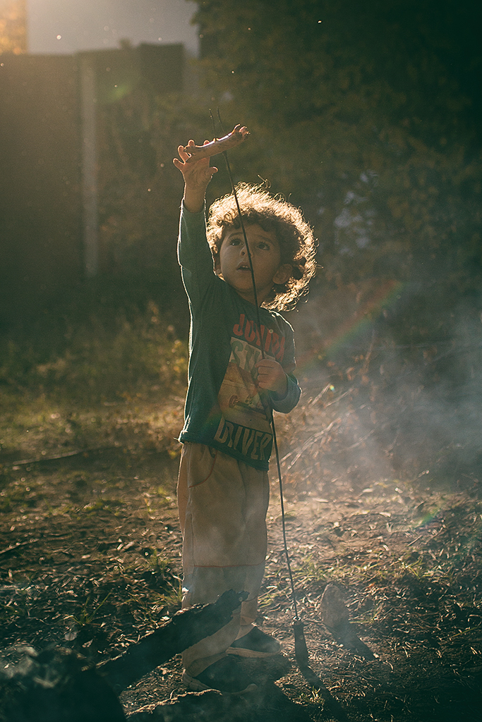 Photographing kids against the light: child toasting sausages.